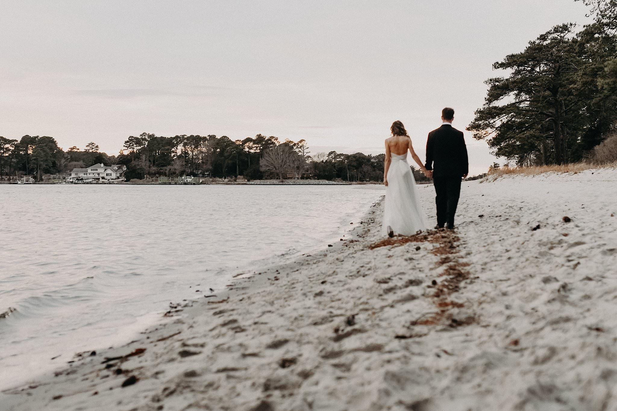 Bride-and-groom-stroll-the-beach-hampton-roads-wedding-photographer-melissa-bliss-photography.jpg