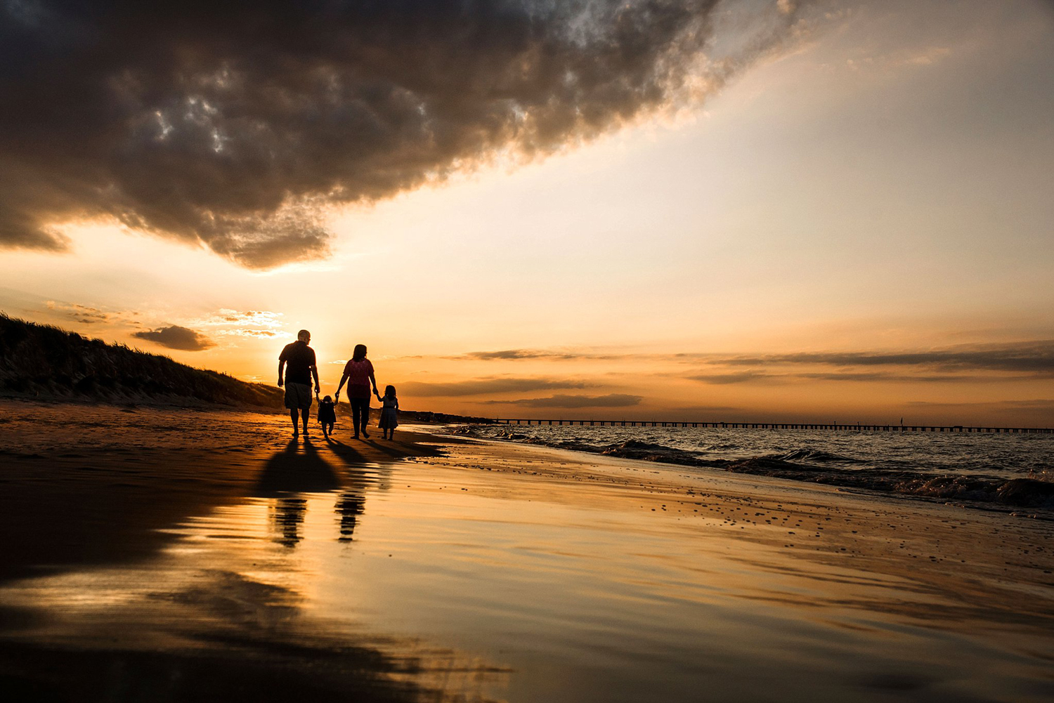 rolling-clouds-sunset-sky-family-silhouette-on-the-beach-melissa-bliss-photography-virginia-beach-photographer.jpg