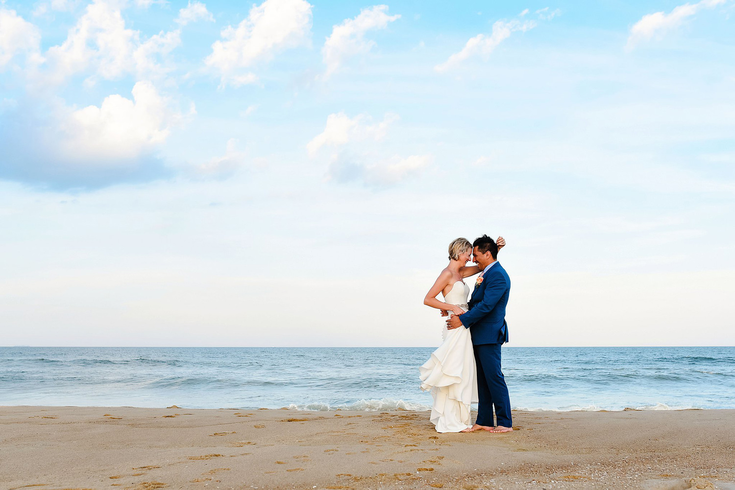 bride-and-groom-dancing-on-beach-blue-sky-beach-wedding-melissa-bliss-photography.jpg