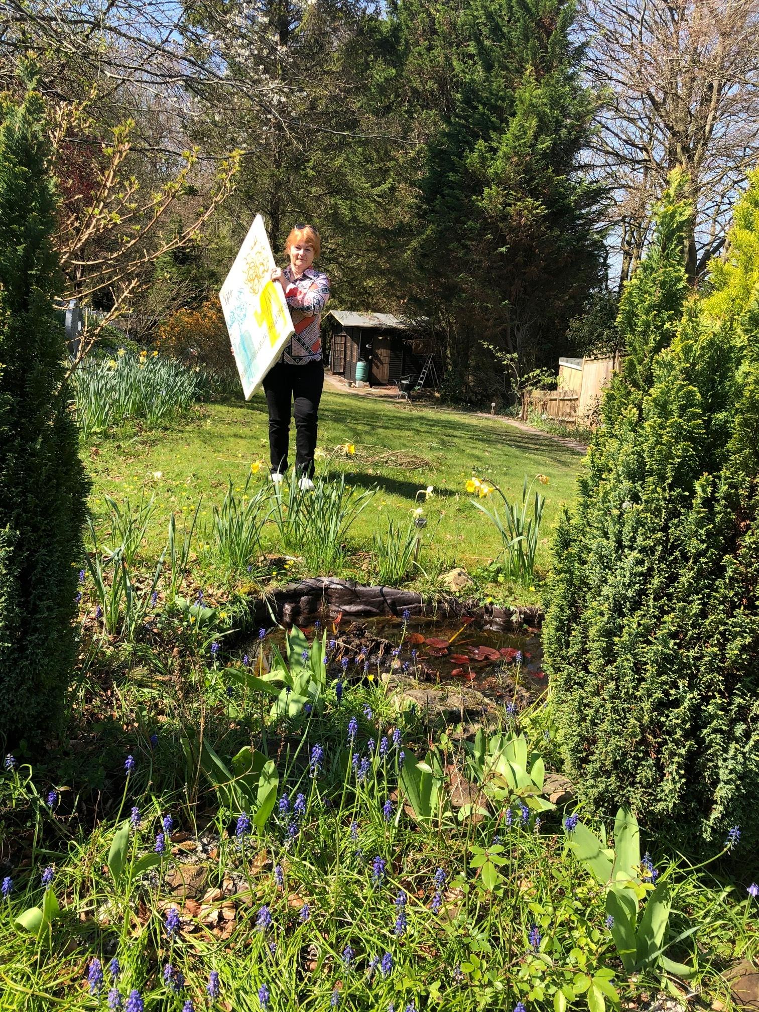 Rachel Williams trekking down the garden with her paintings