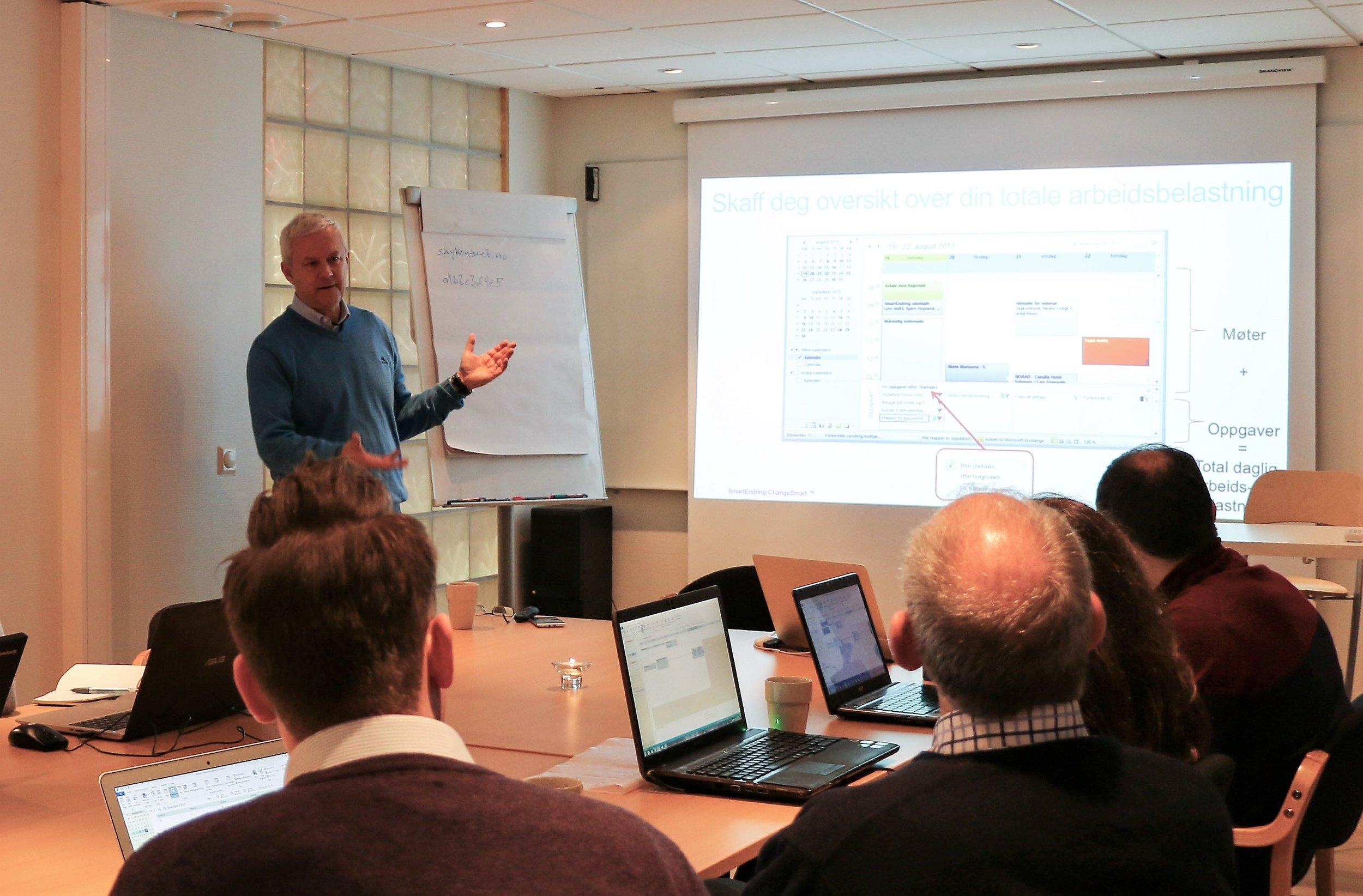 Bilde viser mann som presenterer PowerPoint i møte