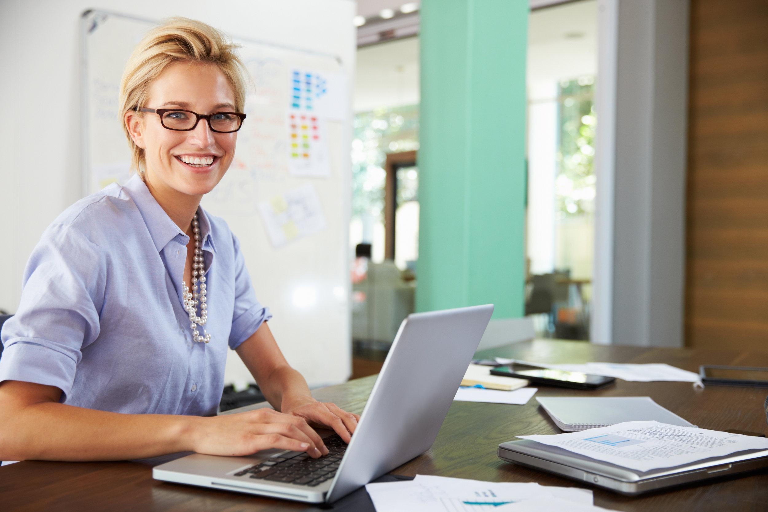 Kvinne ved skrivebord som jobber på PC