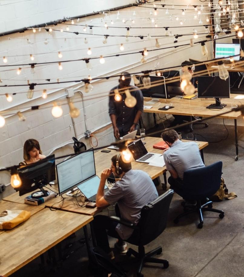 Bildet viser en gruppe som samarbeider rundt et bord med hver sin PC