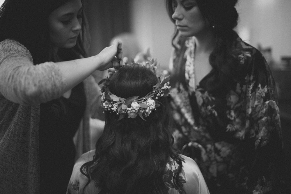 Hairstylist putting flower crown on bride