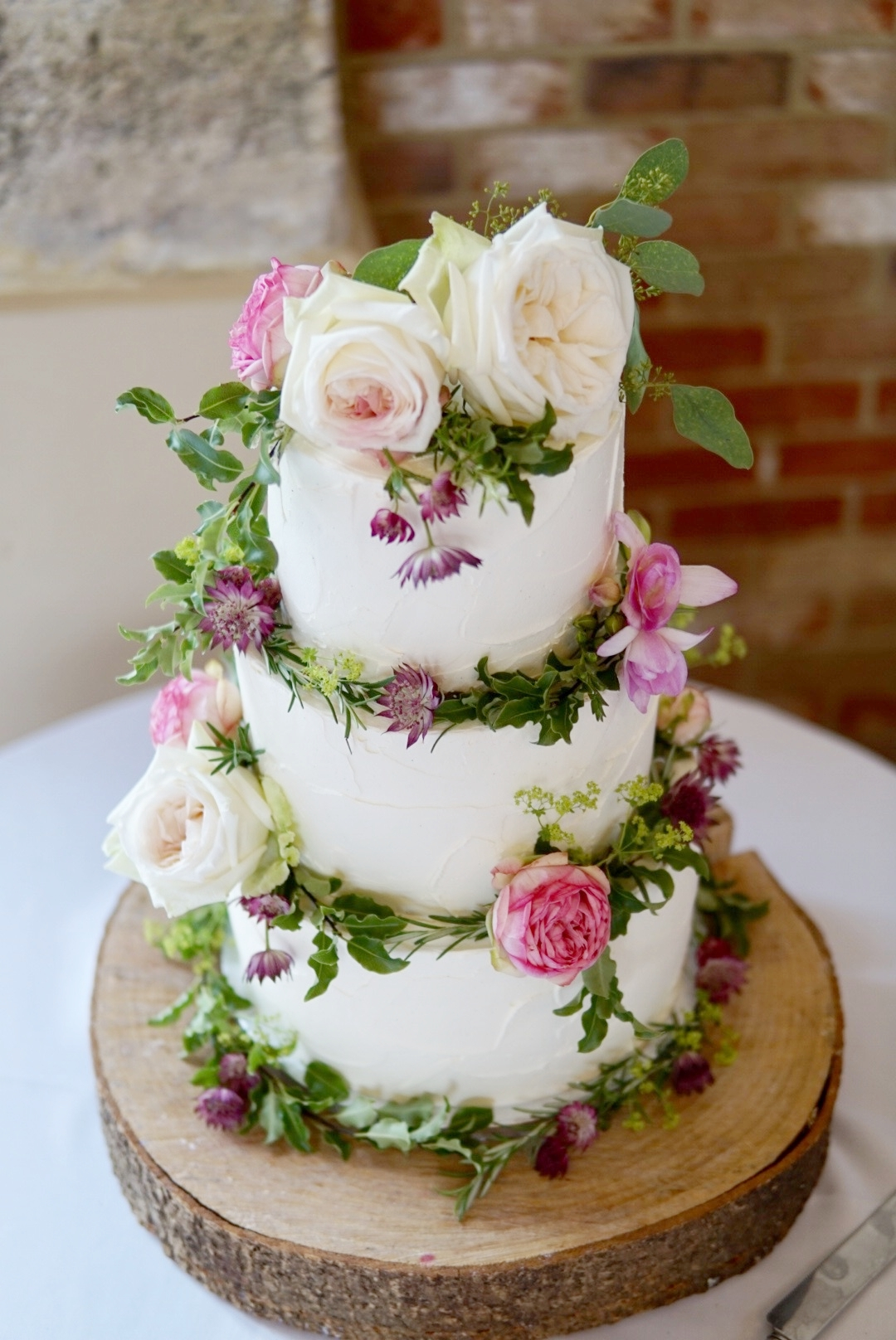 3 Tier Textured Buttercream Wedding Cake with fresh florals and foliage.