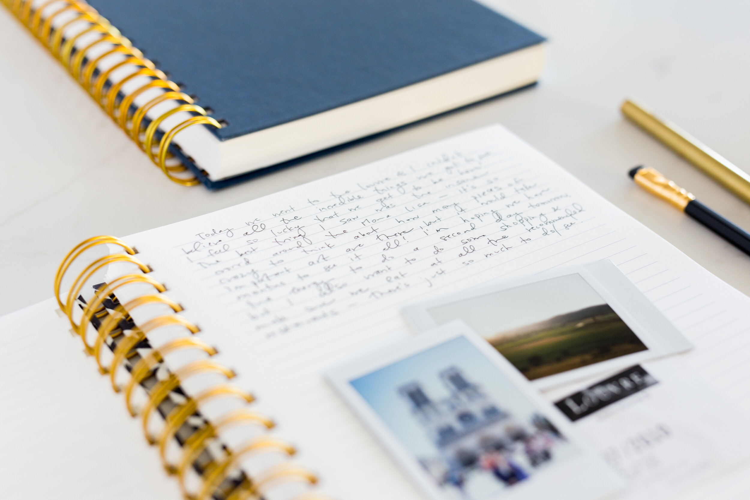 Image of Golden Coil planners with journal entry and instant photographs