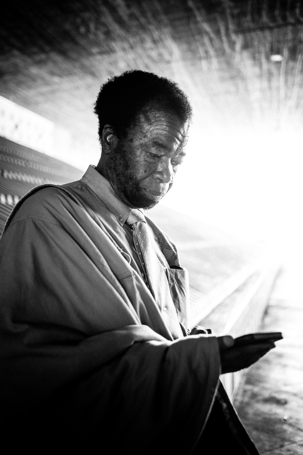 Moment Seven: The luminous light at the end of the tunnel, his contemplative and peaceful look, and even his jacket over his shoulder like a philosopher's tunic.  Is that a book or a phone?  What's the difference nowadays anyhow?  Here, Johnny strikes us as a prophet of South Central...What's the good word, Sir?