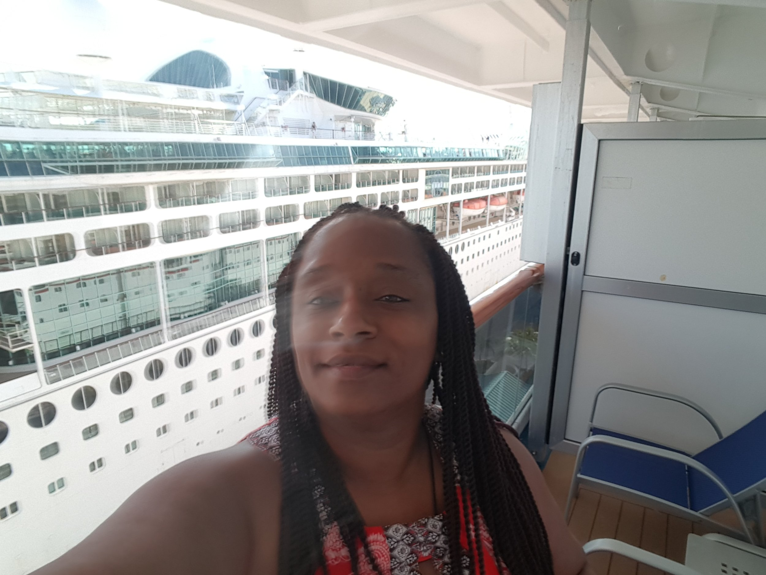 Me on my Carnival Splendor balcony with Carnival ship behind me in Nassau, Bahamas