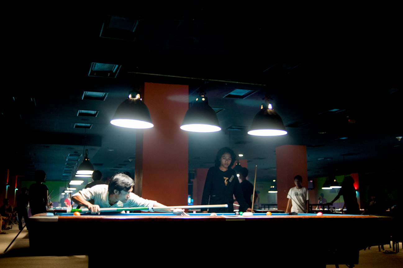 Fais takes a shot in a lurid pool hall in Yogyakarta. Most PMII members, like many Indonesian students don't drink alcohol. Far more time is spent hanging out at open-air cafes or pool halls.
