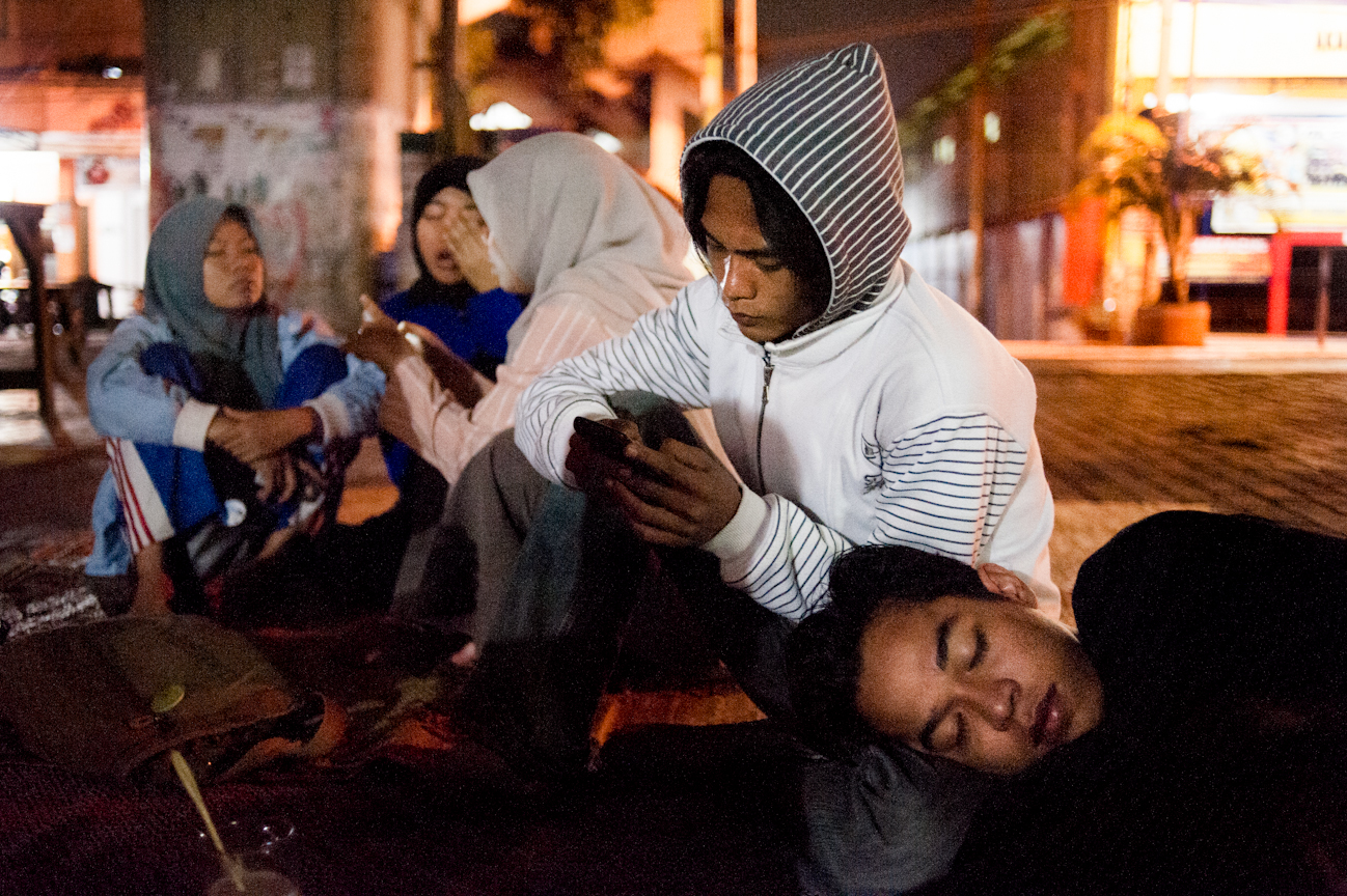 Navic rests his head on the knee of Imam's knee after eating and hanging out late into the night at a food cart under a highway overpass in Yogyakarta.