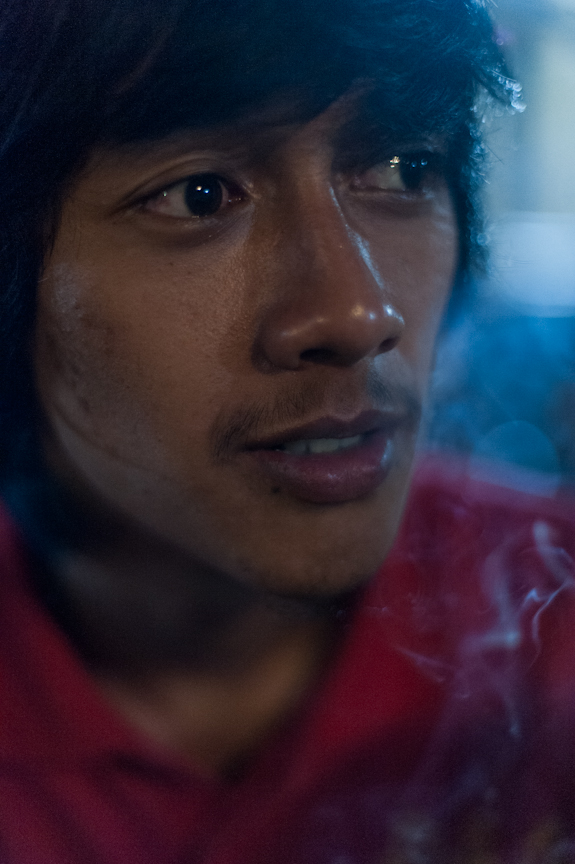 Gatot listens to his friends play music at Cangkir Poetih, a cafe in the neighborhood.