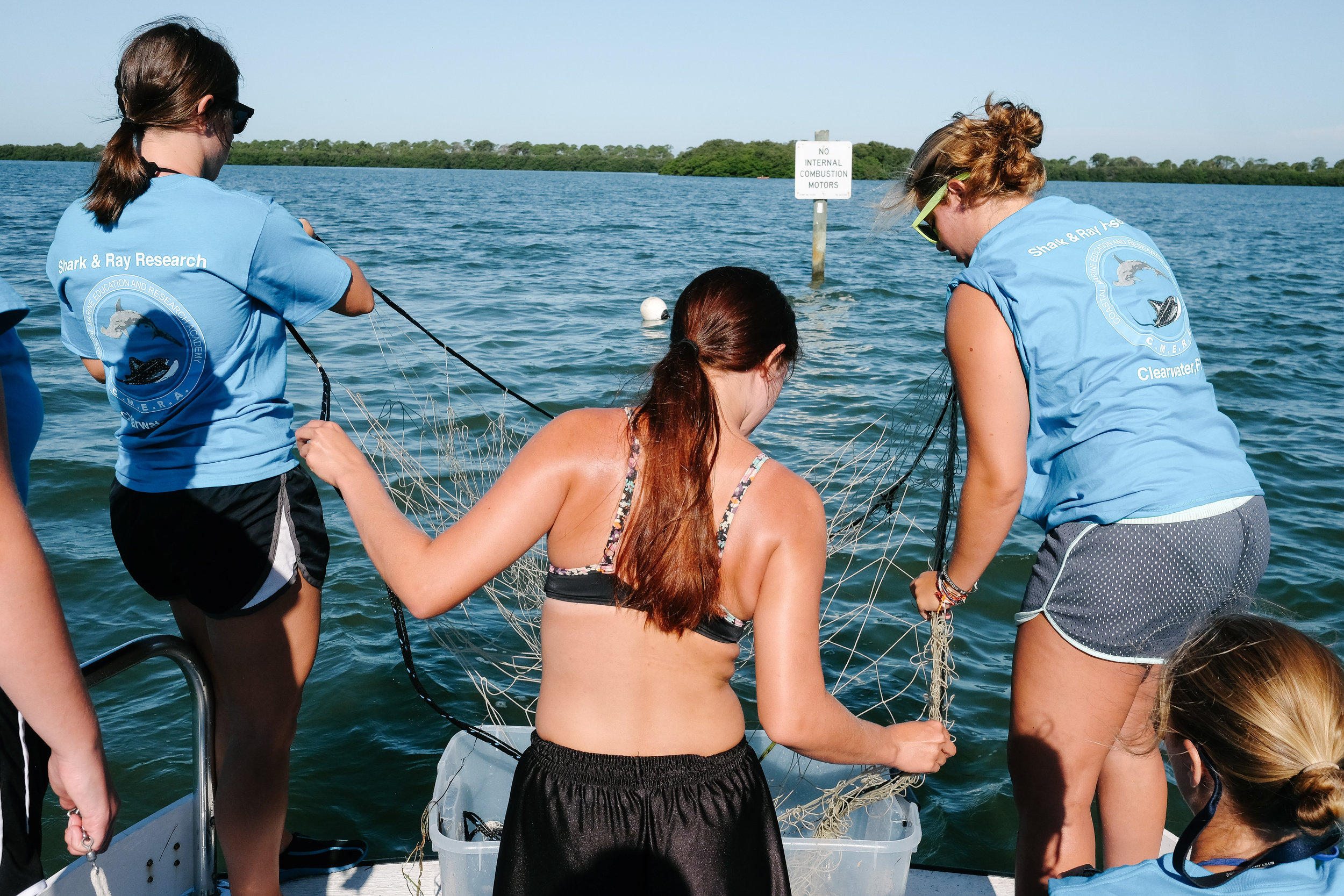 Three CMERA students set a 200-foot tangle net in the water. The net is designed to catch larger marine animals like rays, while allowing smaller fish to simply swim through it.