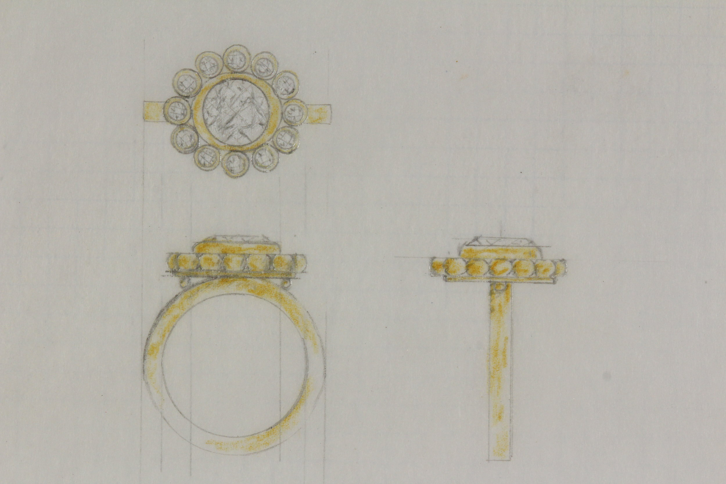 Design Process - In all her high karat glory, this engagement ring was hand fabricated in 22 karat gold. 14 bezel set diamonds encircle a large round brilliant cut diamond on a hat bezel. It also features granulation, a hammer texture and satin finish, all applied by hand. It was designed to accommodate a flush fitting wedding band, making it a very unique wedding set.