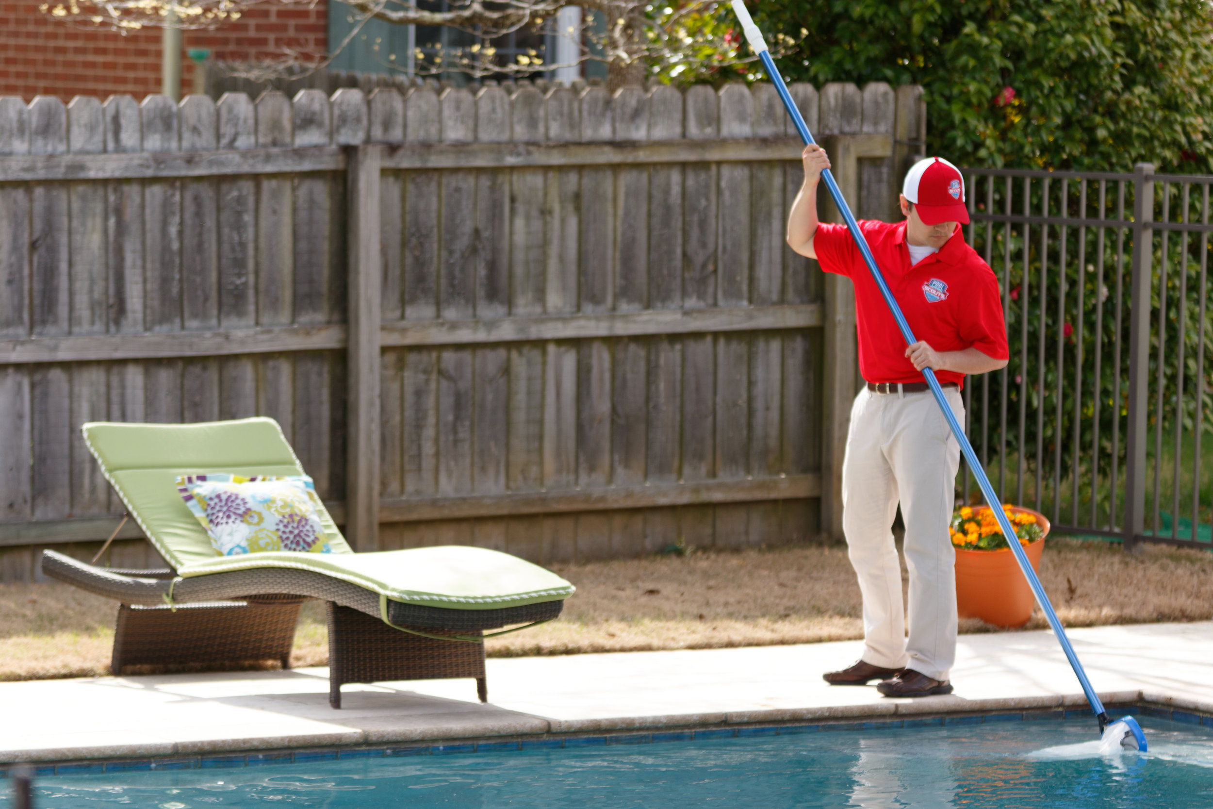 Pool Scouts technician skimming a pool