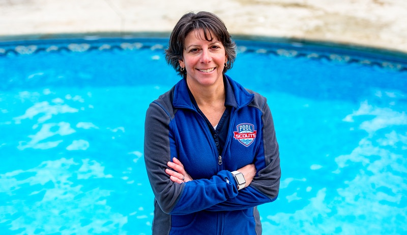 Pool Scouts owner Tiffiny Consoli standing in front of a clear blue pool