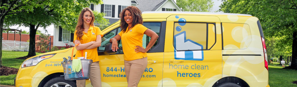 Home Clean Heroes female technicians standing in front of yellow van at customer's house