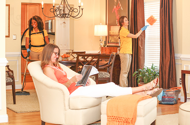 Woman reads magazine with feet propped up while Home Clean Heroes cleans her house