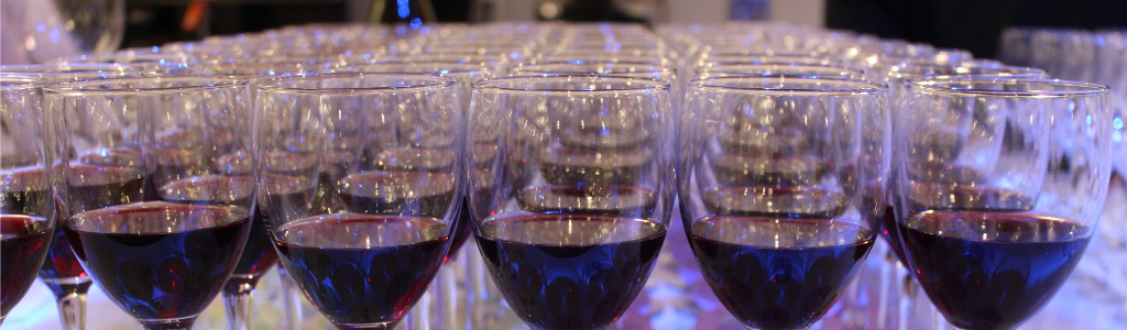 Many glasses of red wine lined up in a row