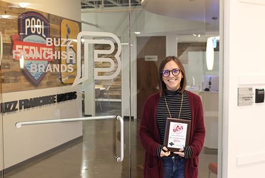Cait smiling with award at BFB office