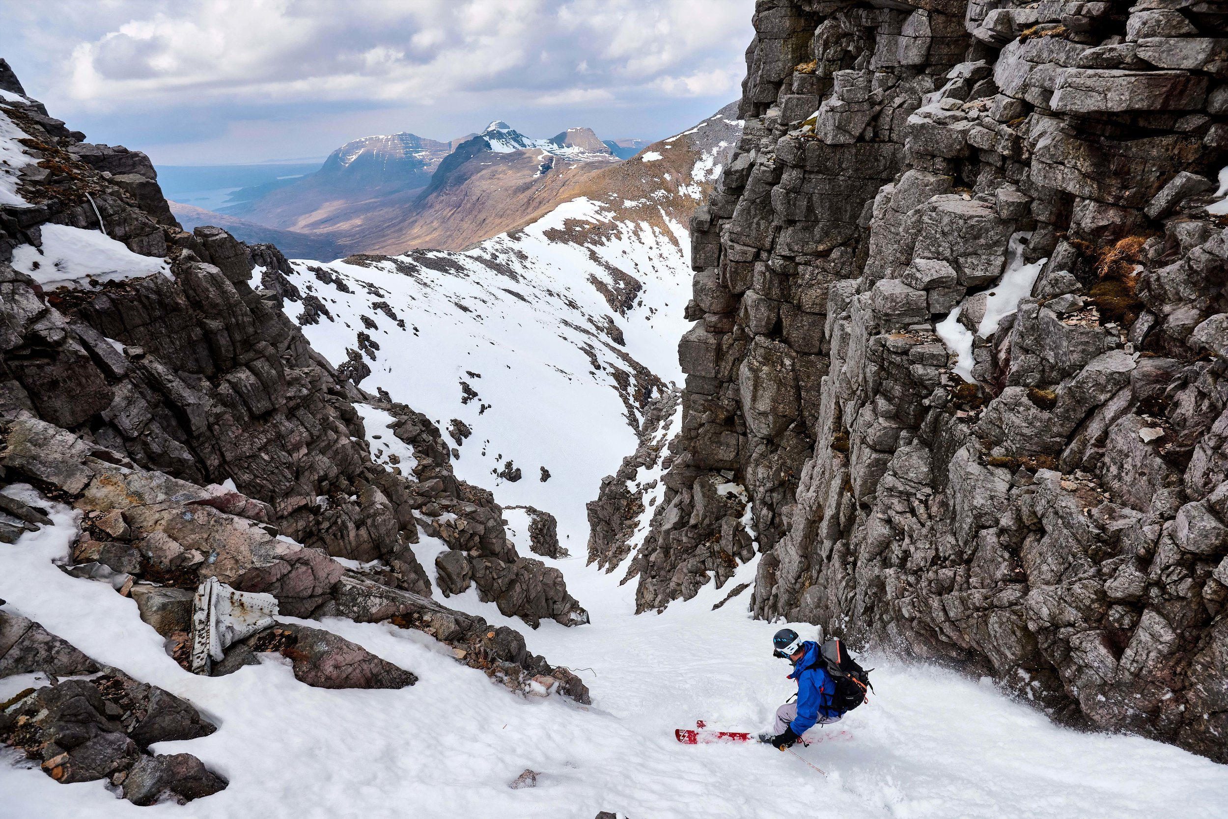 Scott skiing the narrow upper section of 'Fuselage Gully' on Beinn Eighe. In 1951, a Lancaster bomber crashed directly below the summit of Còinneach Mòr, one of the tops of Beinn Eighe and the gully is named after the wreckage which now sits within it (some of which can be seen in the photo). In lean snow conditions, a large propellor which is part of the wreckage can require an abseil to bypass, however on this occasion it was completely banked out, with only the top 30cm or so visible.