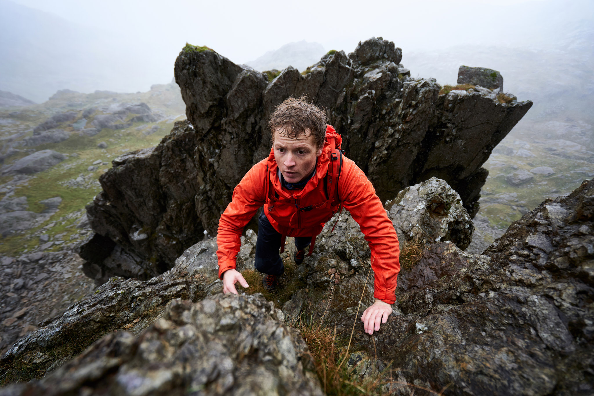 Calum Muskett scrambling up a sopping wet Clogwyn y Person Arête