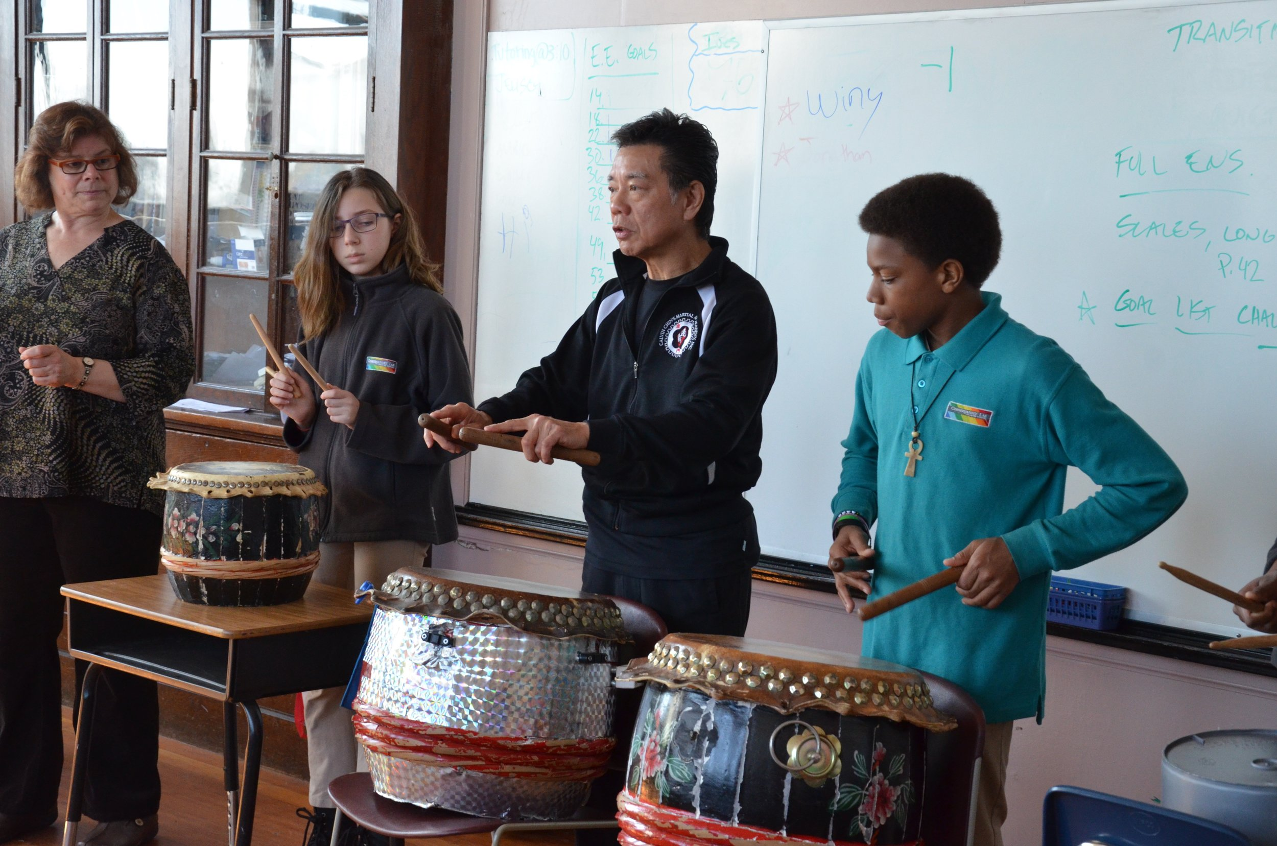 Students learning to play Chinese drums as part of an expedition on China and the Silk Road.