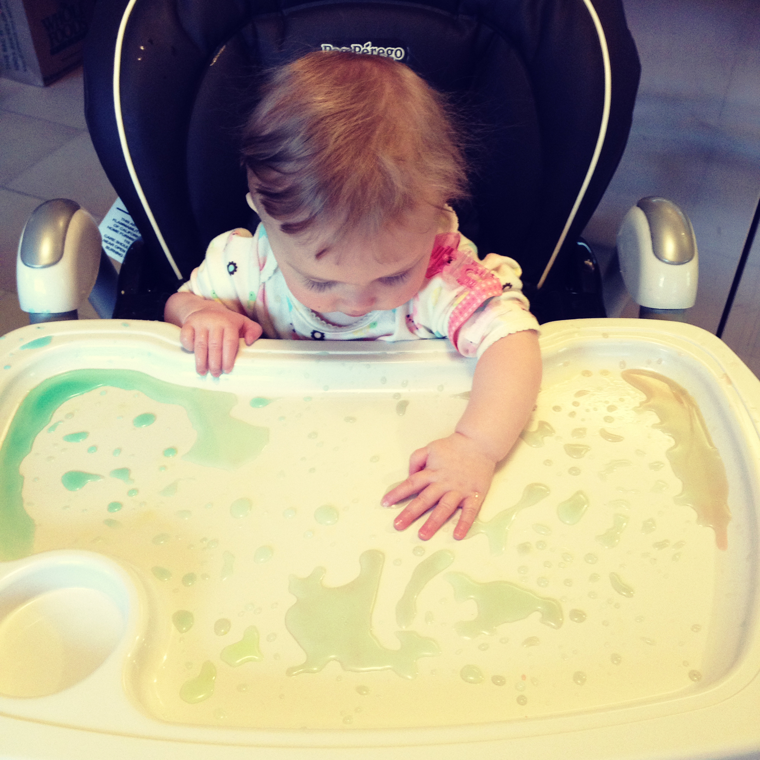 My daughter exploring watercolor droplets on her tray, age 8 months
