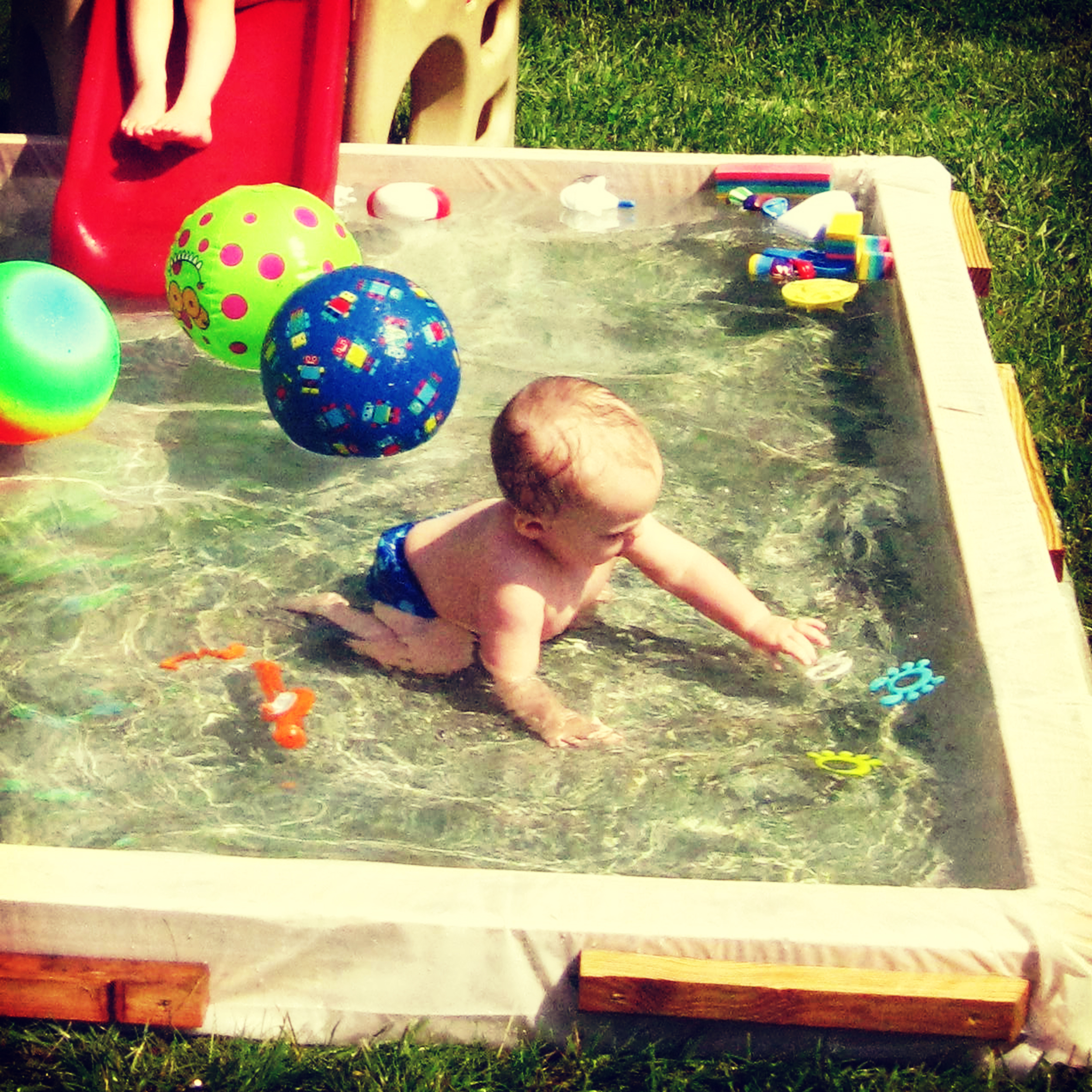 My son playing in the kiddie pool my husband built.