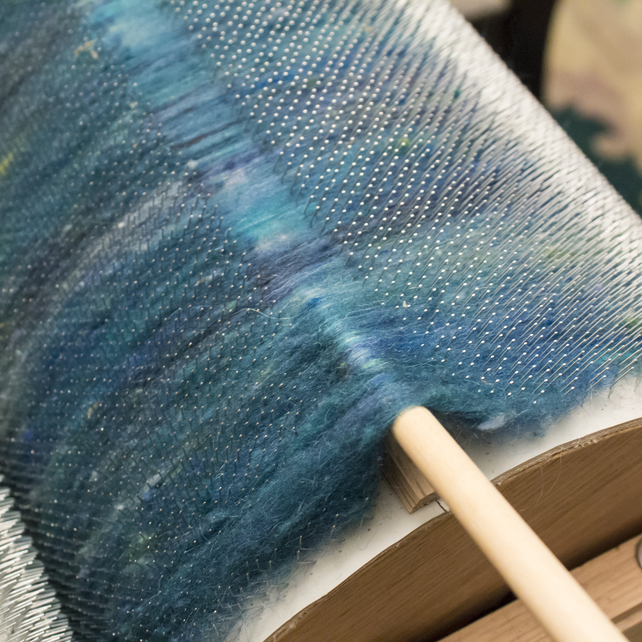 Using a doffing stick at the carding cloth seam. This is the strip you will need to pry up should you need to replace your cloth. Do not use your doffing stick anywhere else on the carder to prevent unnecessary damage.
