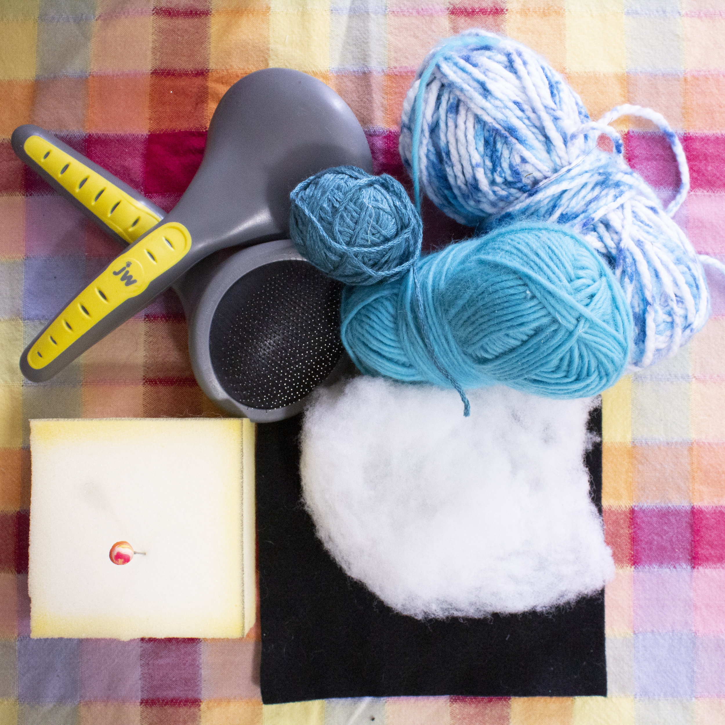 Clockwise from top left: pet brushes, non-wool yarns, poly-fil (on top of craft felt), foam, felting needle