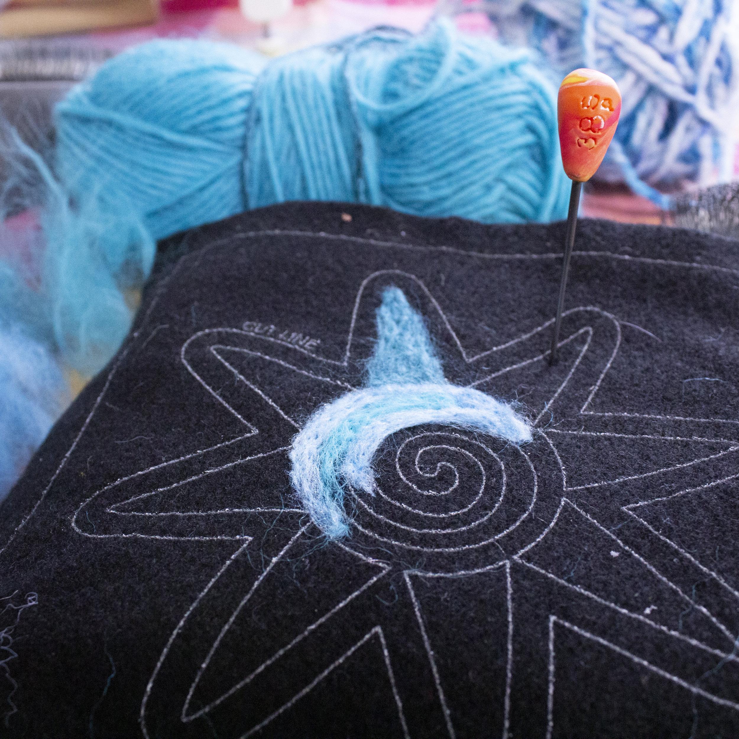 2D needle felting on an applique piece on craft felt using reclaimed yarn fiber.