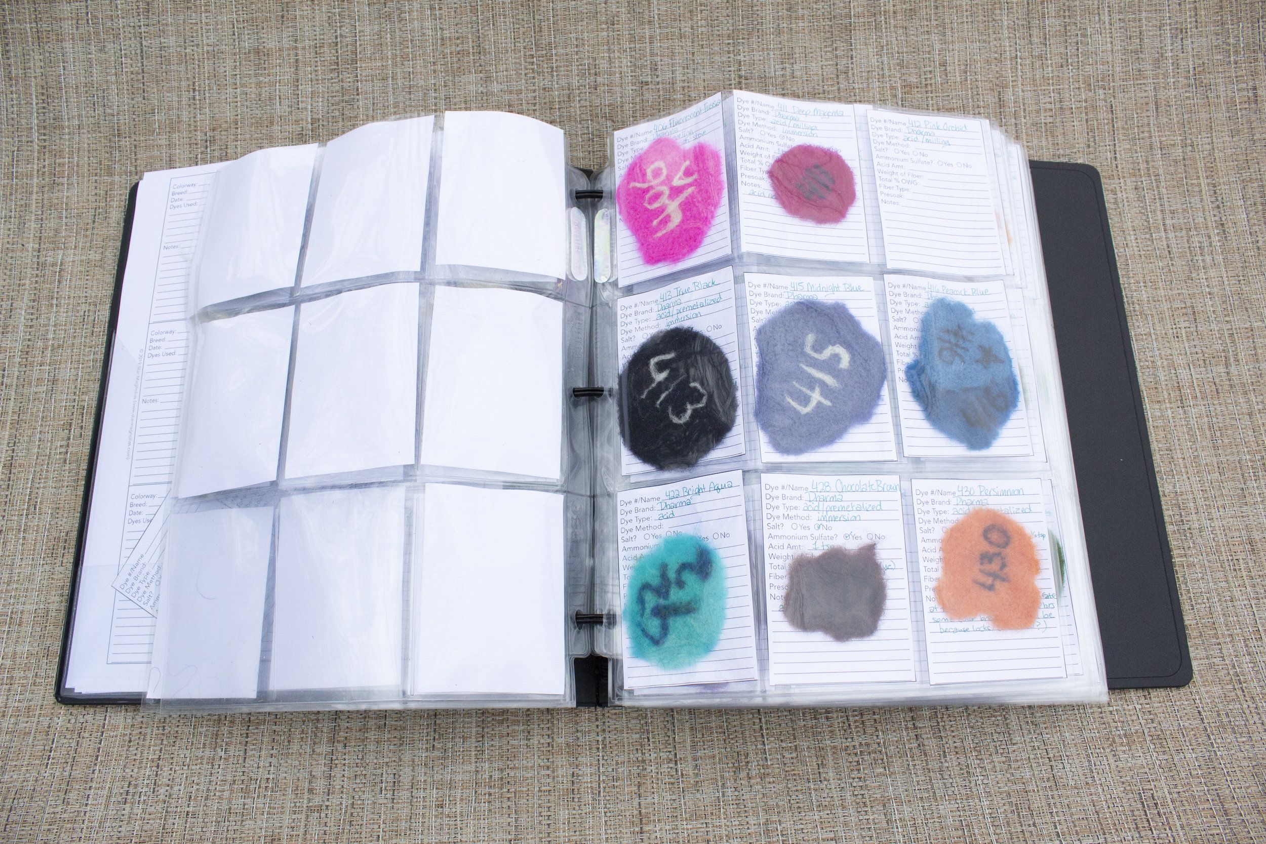 Image: open binder with trading card binder sheets filled with different dyed and numbered needle felted patches, stuffed in the pockets in front of forms describing each sample