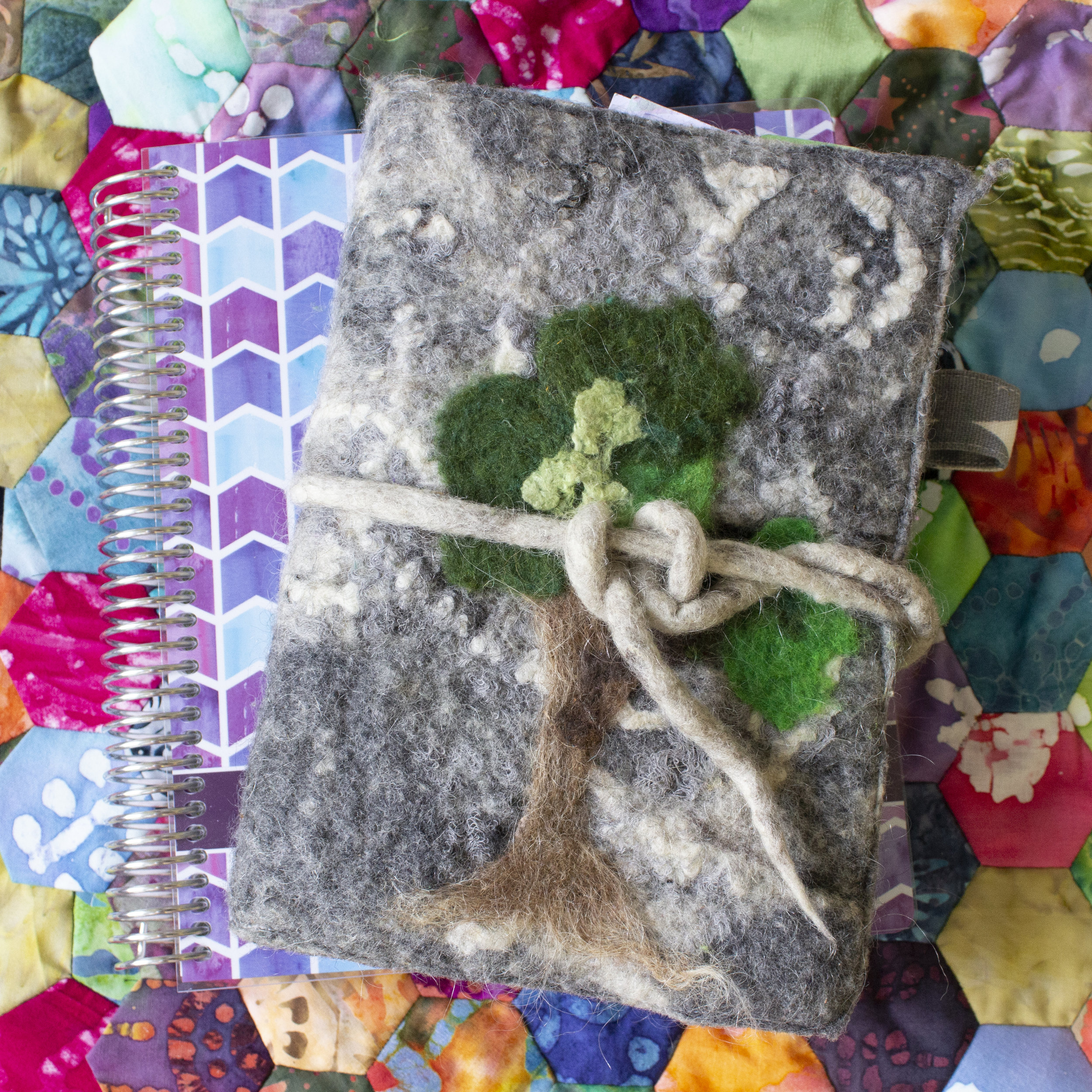My planners - homeschool planner from Plum Paper Planner on the bottom, and my Hobonichi Cousin on top with my first felt journal cover prototype. The tree was a later addition that my daughter felted when she was 5.
