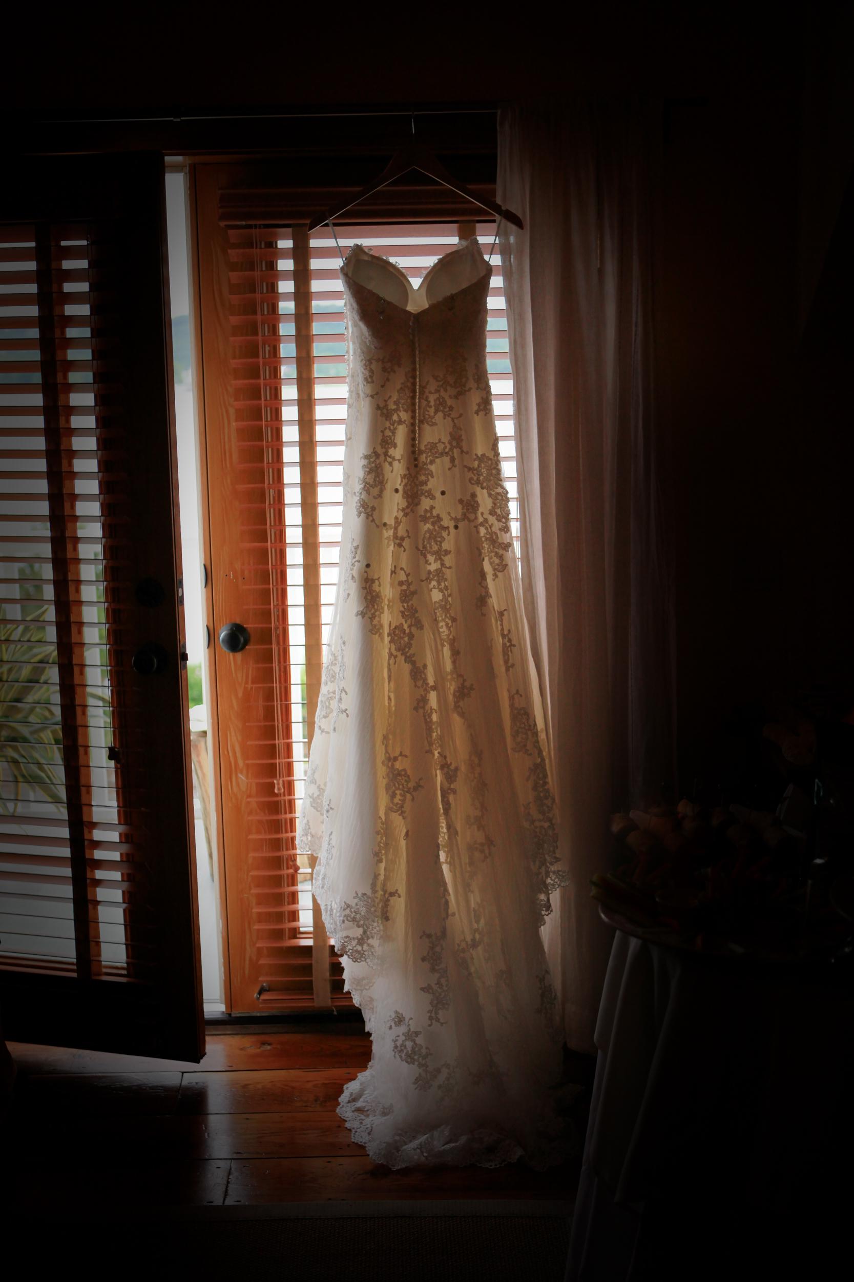 Wedding dress hanging in a barn