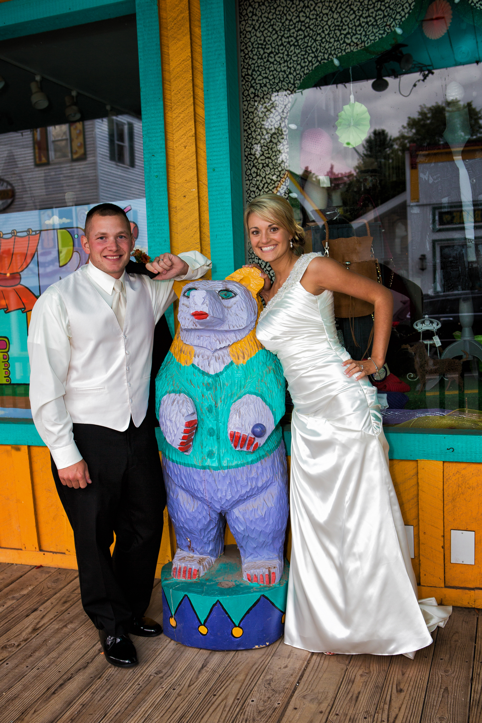 Photo of bride and groom posing with a bear.