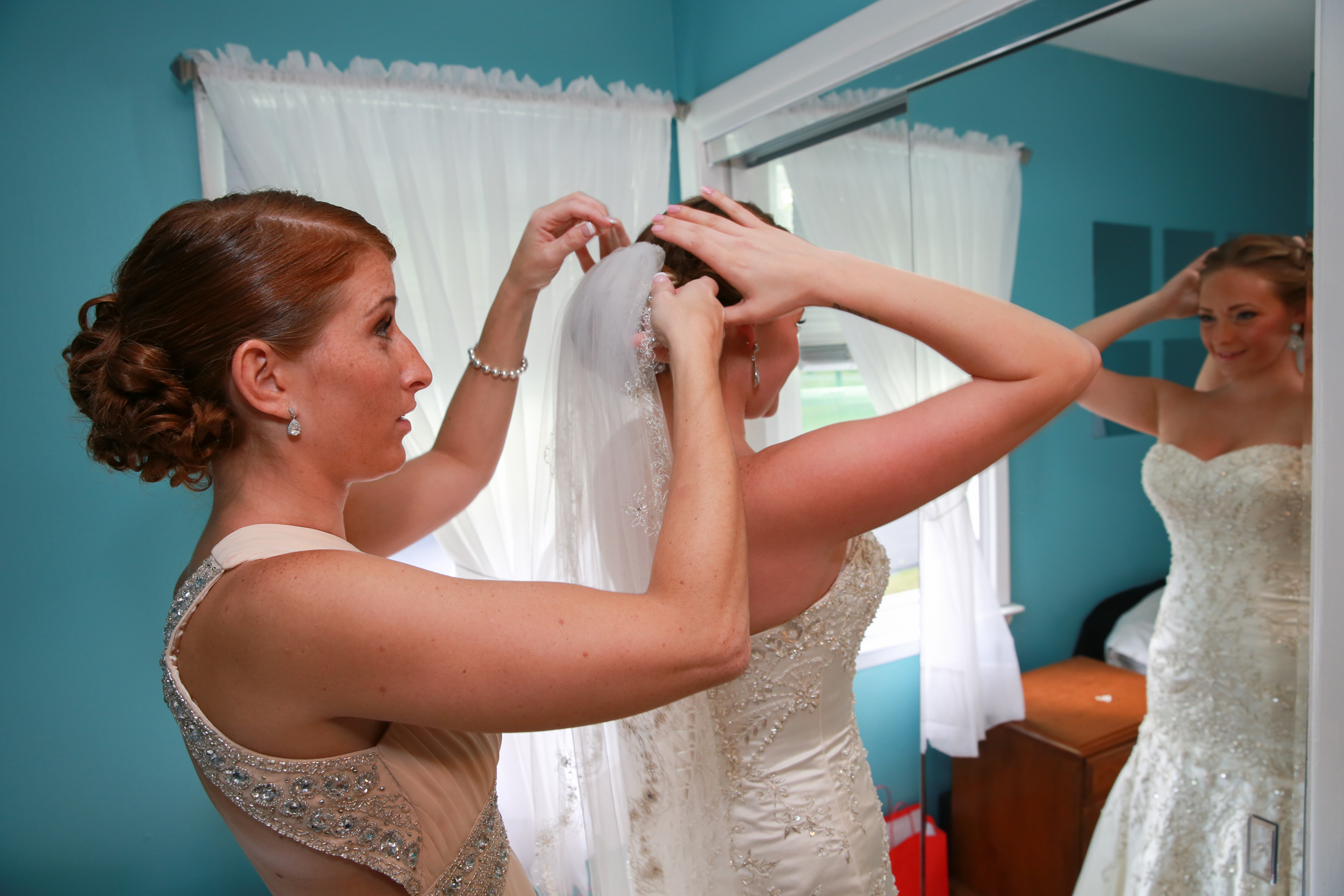Maid of honor putting on brides veil.