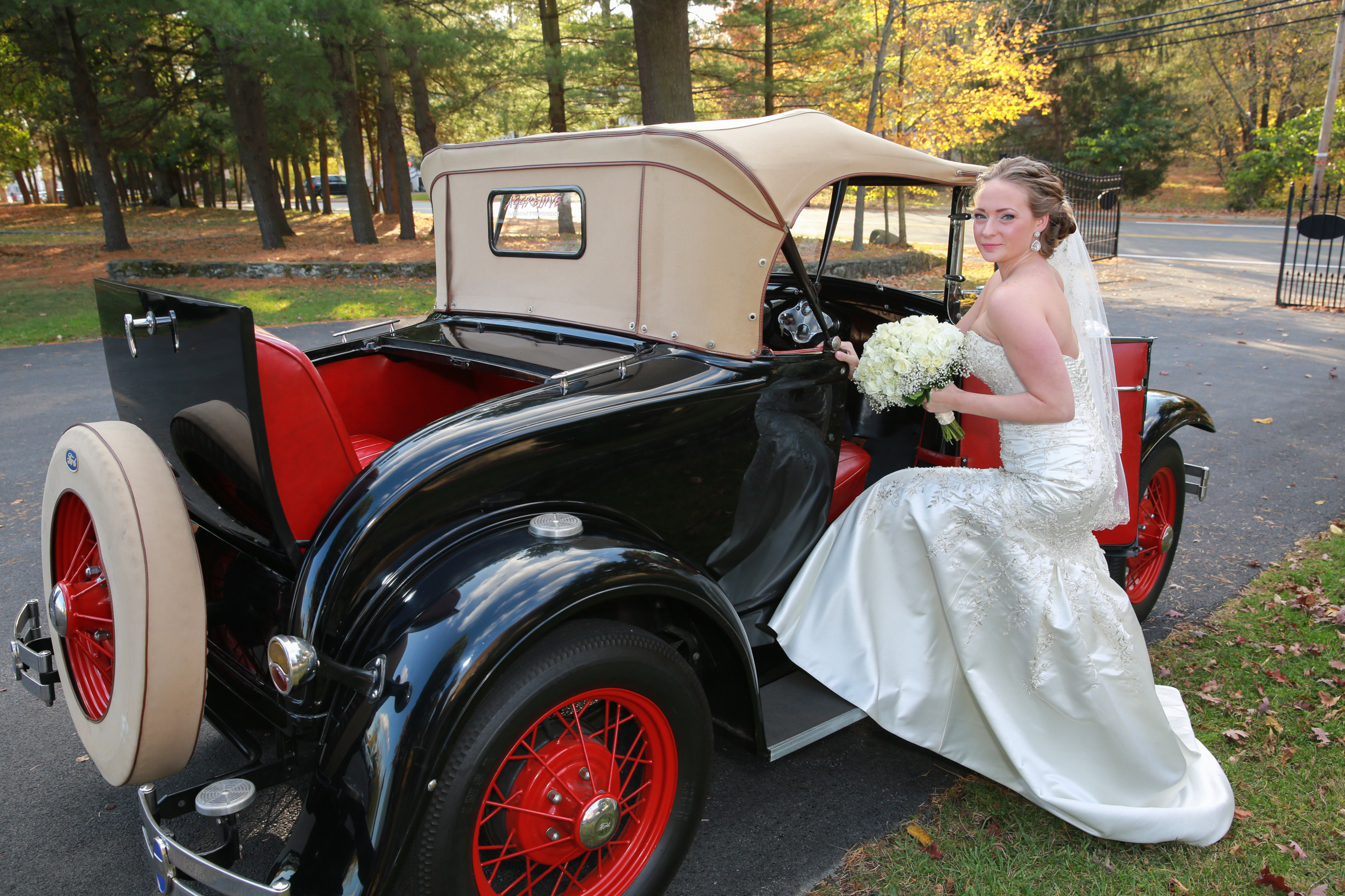 Posed wedding photo of bride and car