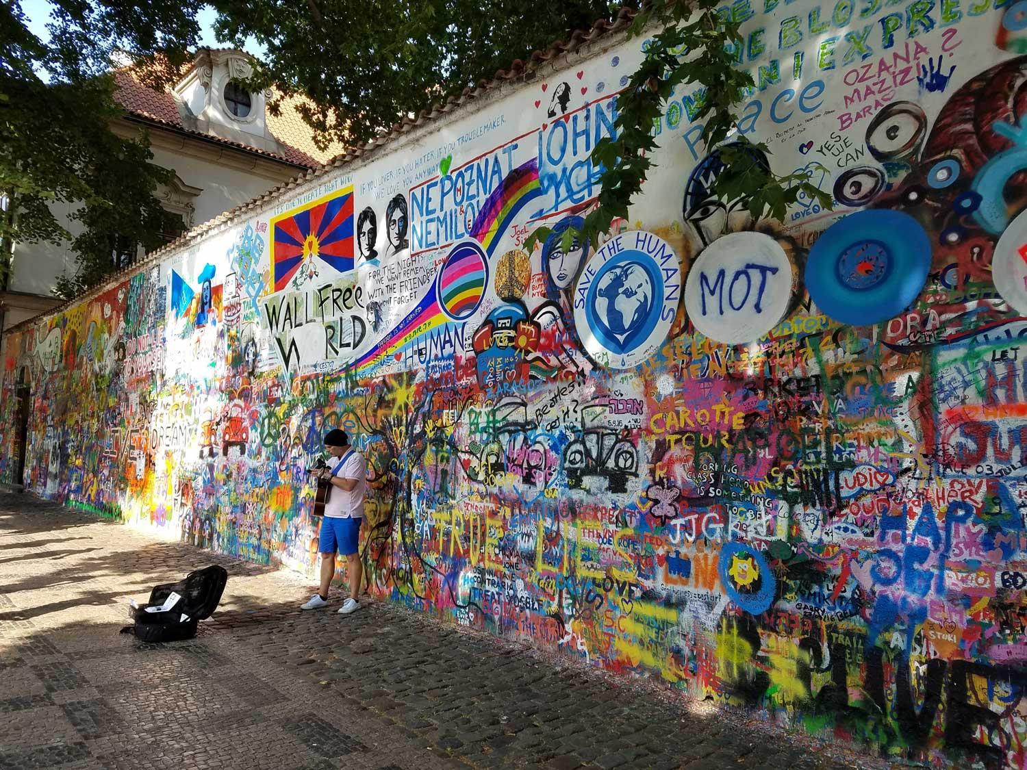After John Lennon was shot, this artwork spontaneously appeared on a wall in Prague. The communists tried repeatedly to paint over it, but the Lennon Wall kept reappearing. Nowadays, something new is added to it every day. The man in the stocking cap is playing Lennon songs for tips.