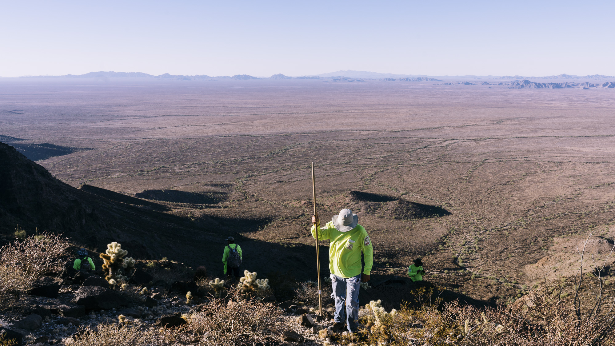 IMAGE CAPTION:  Volunteers from Aguilas Del Desierto scour a mountain peak above the Barry M. Goldwater Air Force Range. Passage through the active firing range, where pilots practice air-to-ground bombing, rocket delivery, and strafing, is the final gauntlet for migrants before reaching Interstate 8, where their guides will have arranged a vehicle pickup.