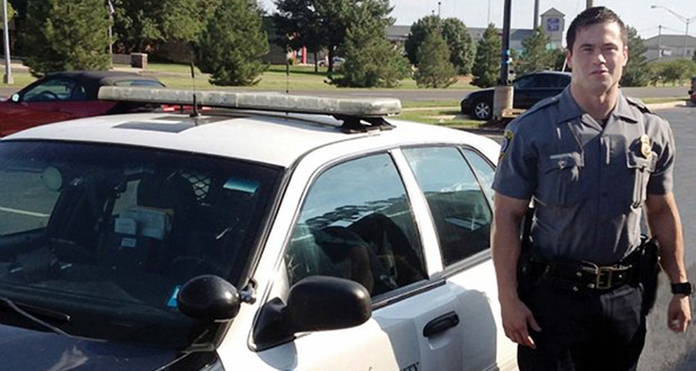 Daniel Holtzclaw standing next to an Oklahoma City Police patrol vehicle.