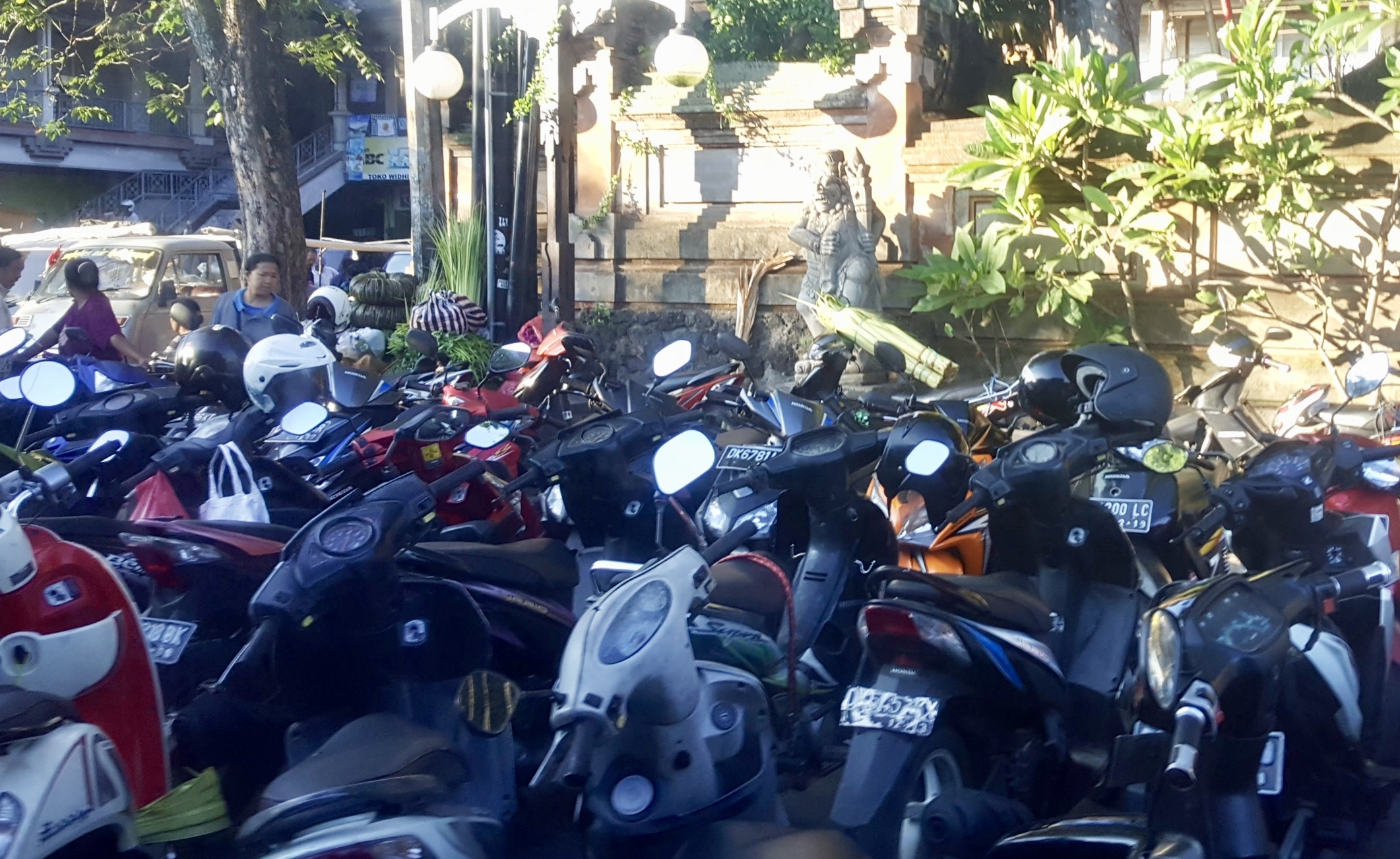 Scooters on the sidewalk, next to the crazy traffic of Ubud, Bali, Indonesia
