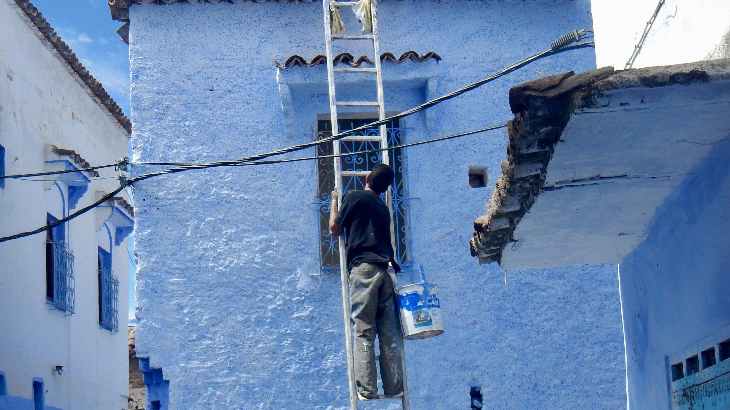 Man painting the walls blue! Chefchaouen, Morocccoui