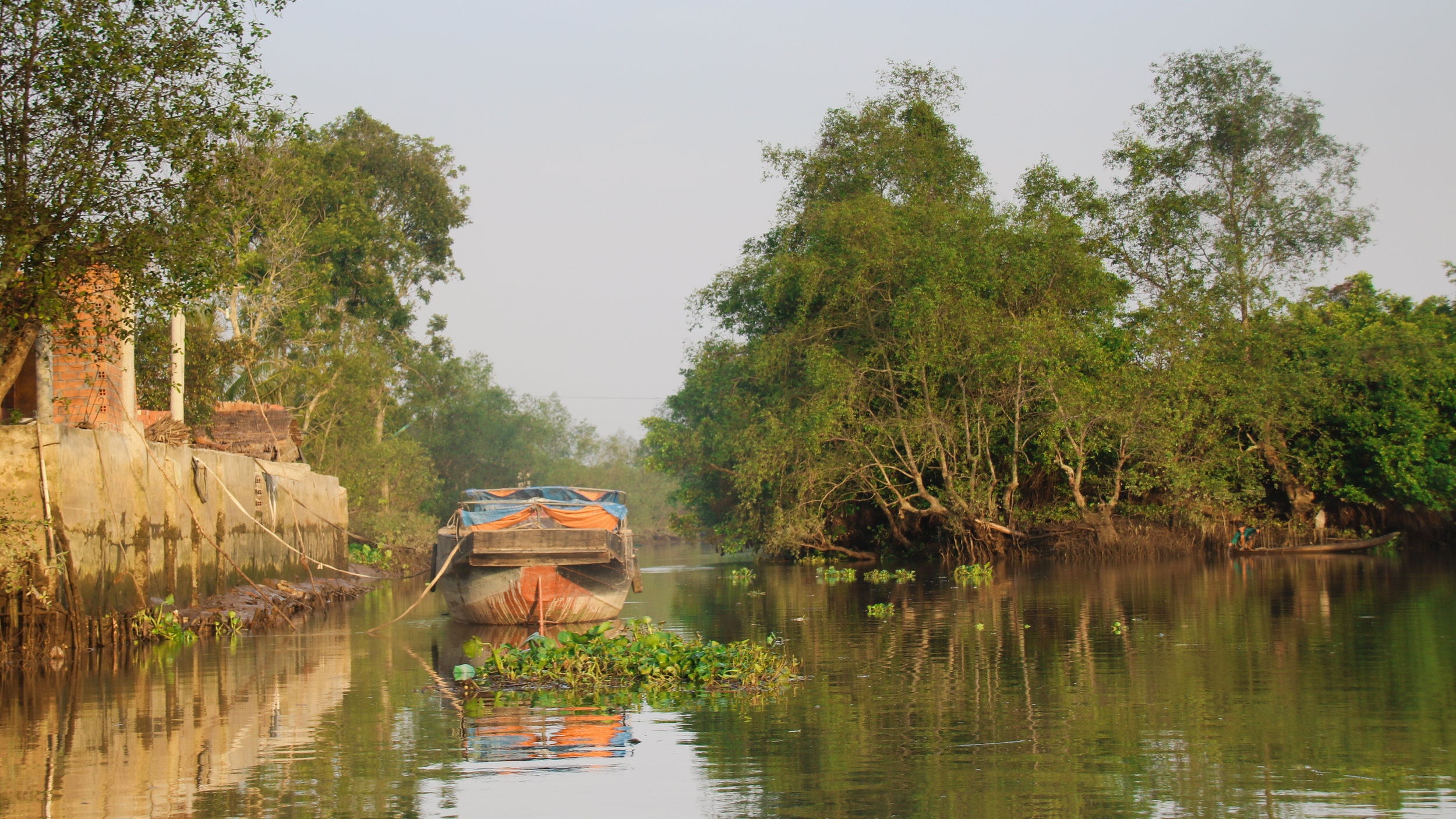 Boat on the river near Vinh Long. 15 really useful things to know before visiting Vietnam. Across Land & Sea