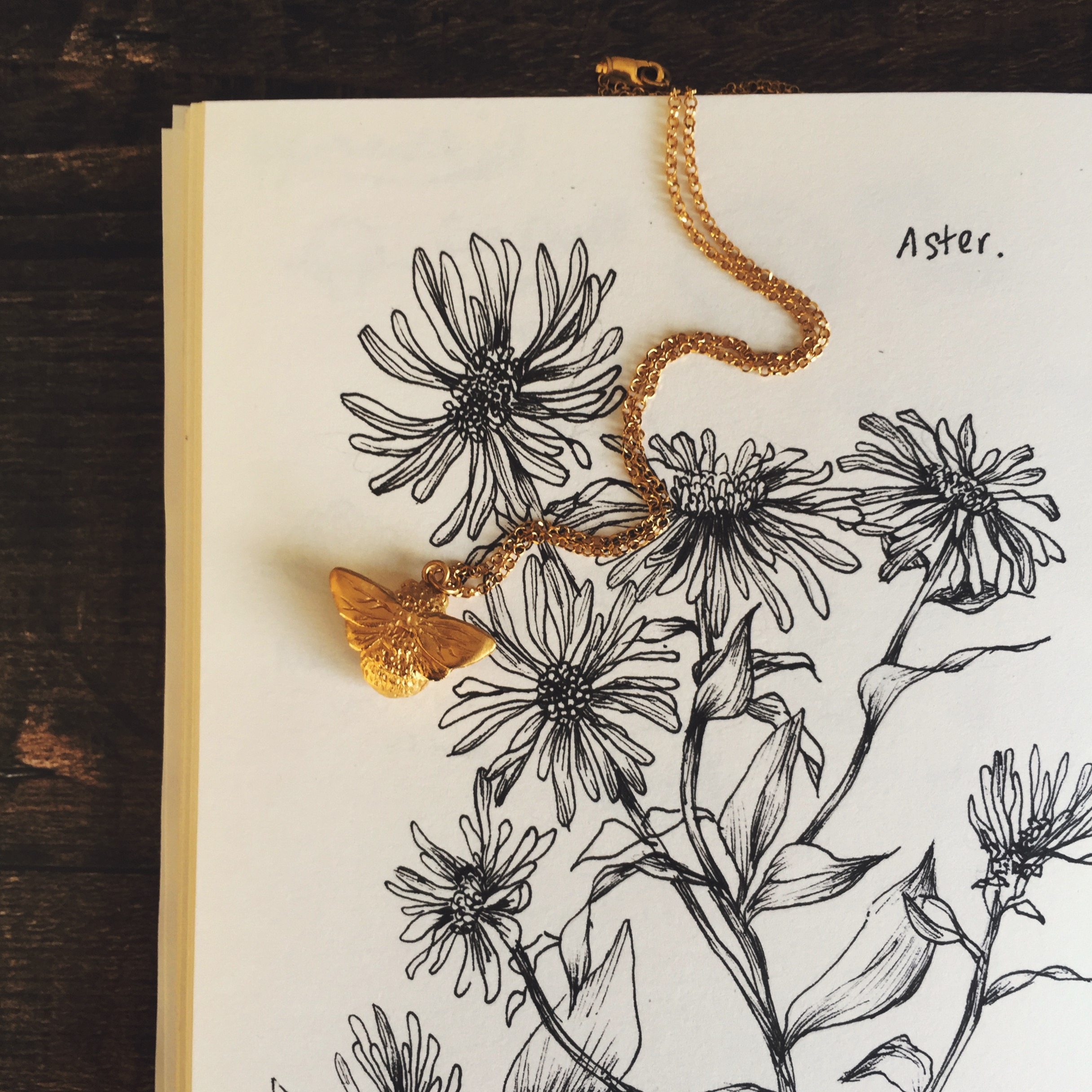 Our buzzy bumblebee necklace against a little sketch of wildflowers.
