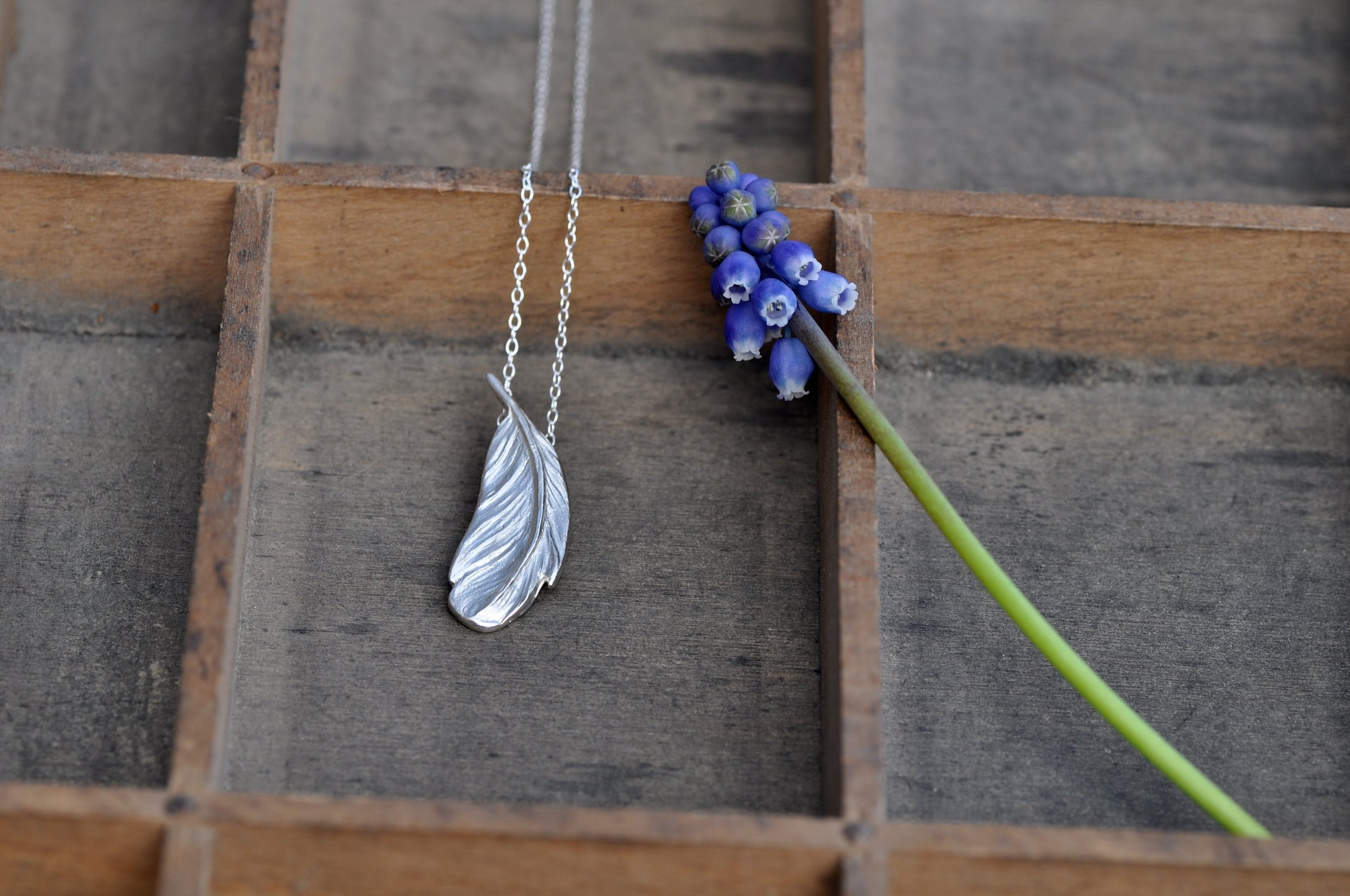 The detailed textures on Denya's feather pendant are exquisite.