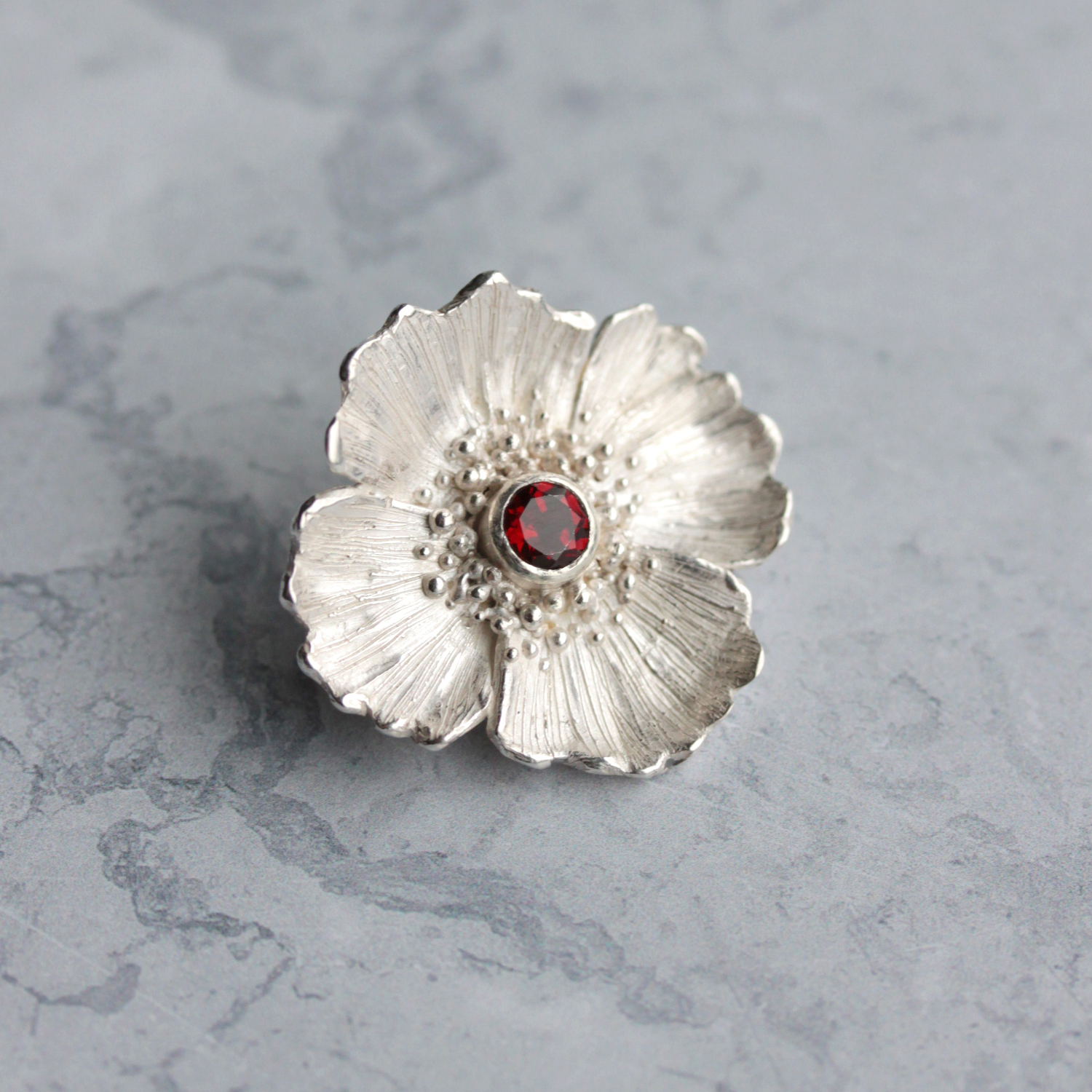 A custom made poppy brooch for a historian, to wear at the World War One centenary events she was attending. A beautiful and symbolic piece, set with a striking red garnet.