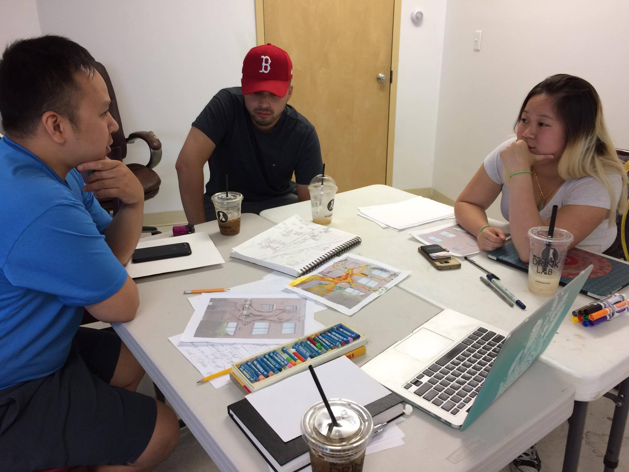 Left to right: Tam, Tony, and Kathy (Photo: Tran)  Artist's at work! In the moment, artist team were discussing how designs could improve!