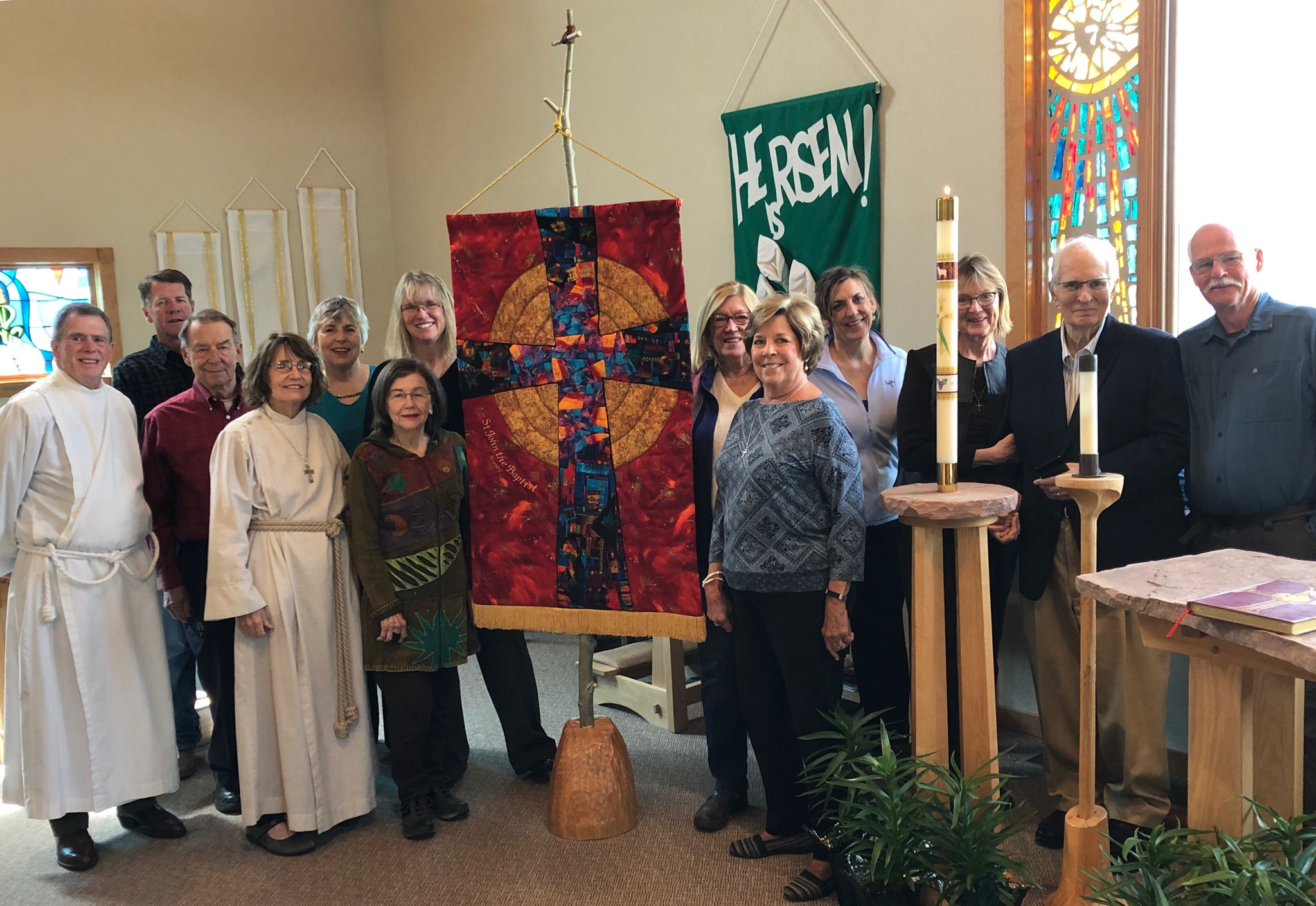 - On May 19, 2019, the new Ceremonial Banner for St. John's was unveiled to the congregation and blessed. This beautiful banner was designed by parishioner Margaret Watts, lovingly sewn and quilted by Deborah Lord Treiber (of the Peaks and Pines Quilt Guild), and dedicated in memory of Ann McLean.Those attending the unveiling and blessing include (from left) Fr. Matthew Frey, David Craig, Lorie Wheeler, Teri Jurgens, Pam Hansen, Margaret Watts, Kay Irvine, Roxanne Singler, Betsy Pettit, Katharine Frey, Sherry Erzinger, Will Wamsley, and Gary Piper.