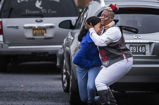 A woman is consoled after she collapses in grief after the memorial for Amy.