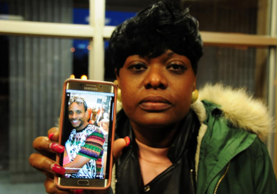 """Lamb's sister holds a picture of Curtis, who is a """"person of interest"""" in the fatal stabbing."""